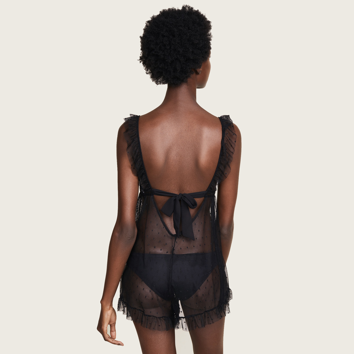 A model (shown back view) wears the black lace Cou Cou Lola tie-back teddy by Only Hearts. It is a sheer polka dot lace teddy with ruffles on the straps and around the bottom of the legs. A princess seam under the bust provides shape and support.