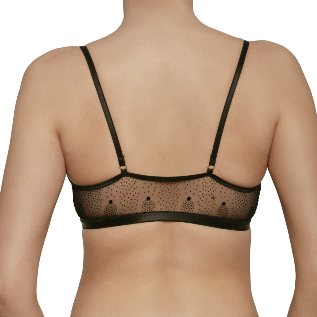 Back view of A model shown waist-up wears Le Petit Trou Estelle bralette. It is made of a sheer black mesh that features a pointillism-style dot pattern.