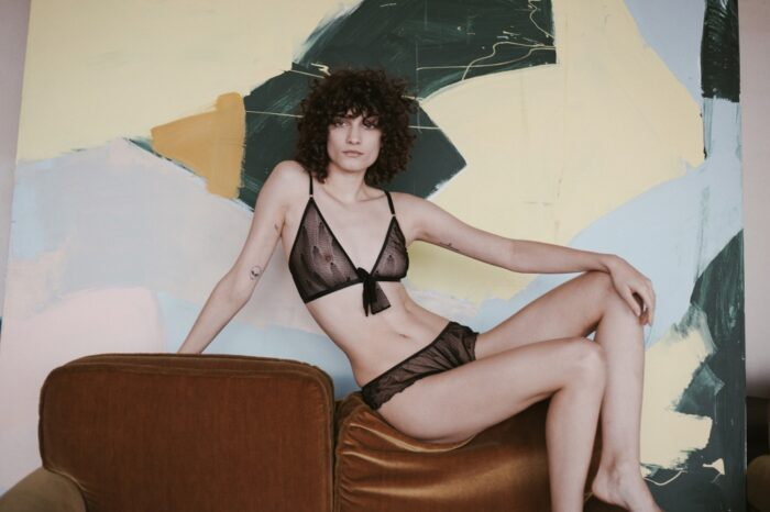 A model sits on a rust colored velvet couch and wears Le Petit Trou Estelle bralette and matching Marine briefs. They are made of a sheer black mesh that features a pointillism-style dot pattern.