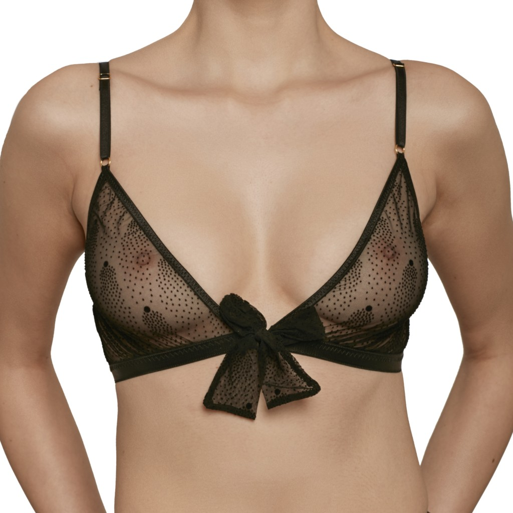 A model shown waist-up wears Le Petit Trou Estelle bralette. It is made of a sheer black mesh that features a pointillism-style dot pattern.