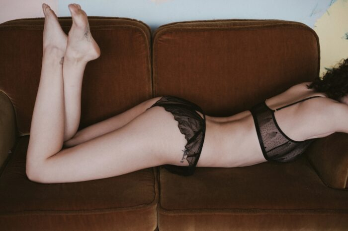 A model lays on a rust colored velvet couch and wears Le Petit Trou Estelle bralette and matching Marine briefs. They are made of a sheer black mesh that features a pointillism-style dot pattern.