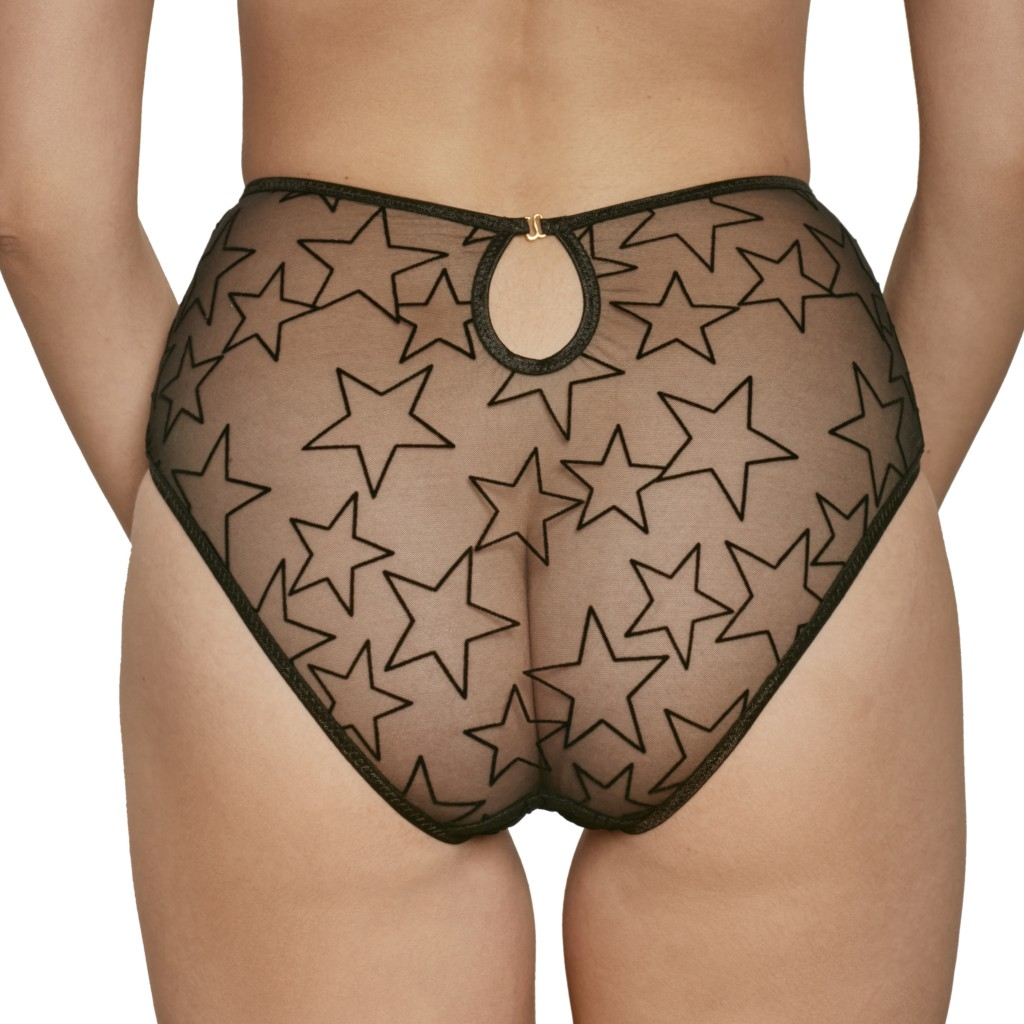 A model shown from the waist down wears the Melanie high waisted briefs by Le Petit Trou. They are made of a sheer black mesh featuring flocked velvet black stars allover, and a small keyhole cutout in the back.