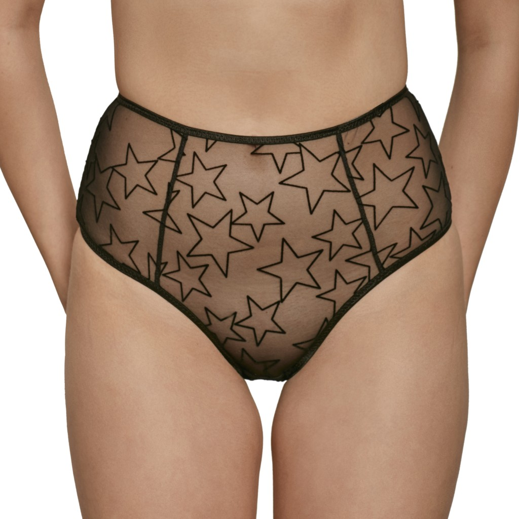 A model shown from the waist down wears the Melanie high waisted briefs by Le Petit Trou. They are made of a sheer black mesh featuring flocked velvet black stars allover.