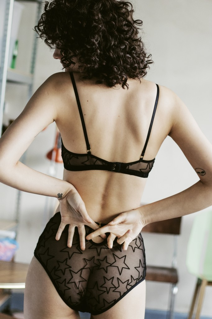 A model (back view) wears Le Petit Trou Audre bralette and Melanie high waisted briefs. The bra and panty set are black and sheer, with velvet stars outlined flocked onto the material. The bralette is a sporty style with no darts.