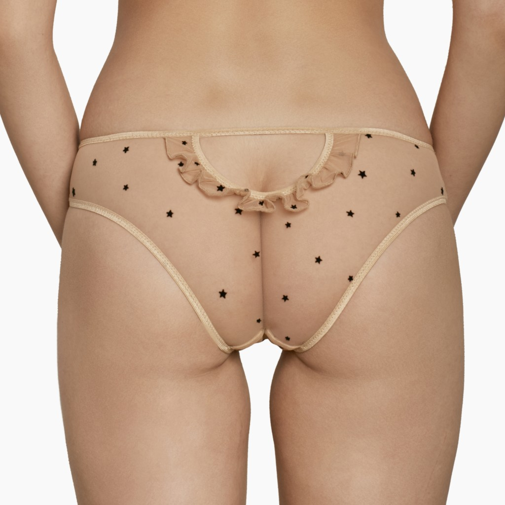 Back view of the Le Petit Trou Sabrina panties. They are made of a light beige mesh and feature tiny black velvet stars allover, and beige ruffle details.