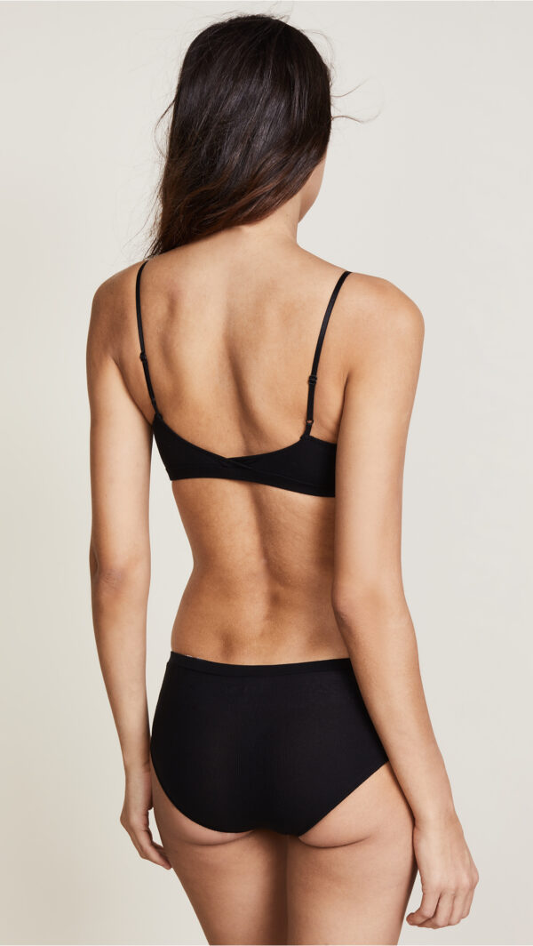 A model (back view) wears the featherweight rib straight bralette in black by Only Hearts. It is a basic stretchy bralette featuring slim adjustable straps. She wears matching black panties as well.