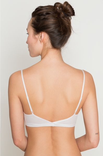 A model (back view) wears the featherweight rib straight bralette in white by Only Hearts. It is a basic stretchy bralette featuring slim adjustable straps.