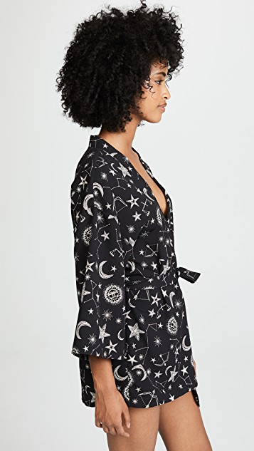 A model shown in a side view wears the Only Hearts Seeing stars kimono robe. It is a dark navy material printed with white and light pink moons, stars and constellations. The robe is a wrap-style and has a matching detachable belt. The robe hits mid-thigh.