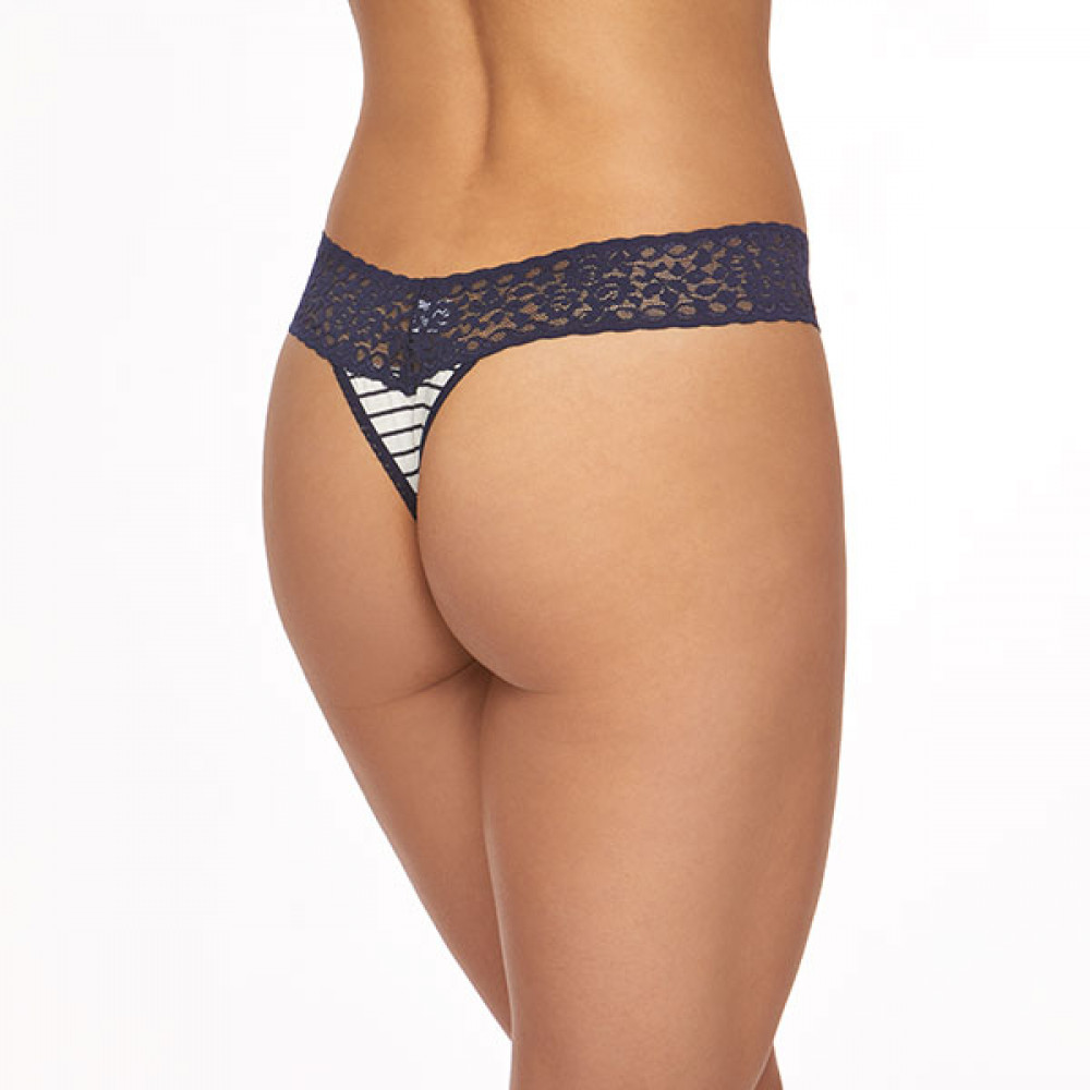 A model is shown from the waist down (back view) wearing the Hanky Panky Jersey Stripe original rise thong panty. The jersey material is white with thin navy stripes and is trimmed in a soft navy lace.