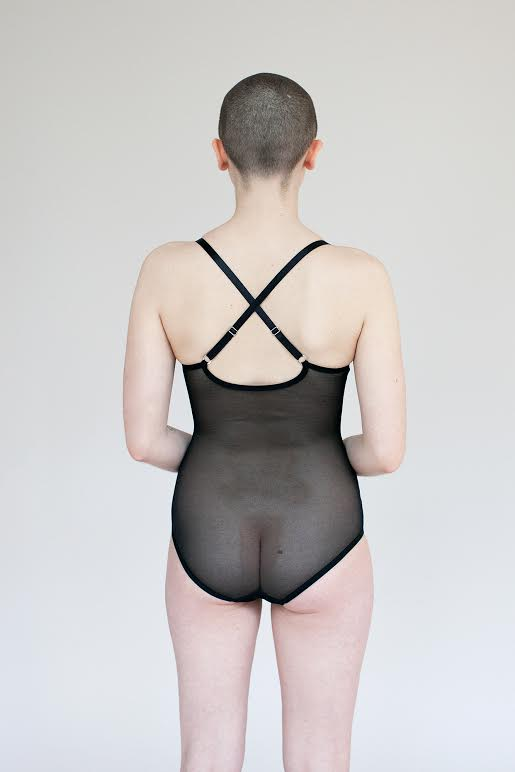 Model facing backwards and showing the back of the black mesh Iona bodysuit. It is sheer and features criss-crossed adjustable straps.