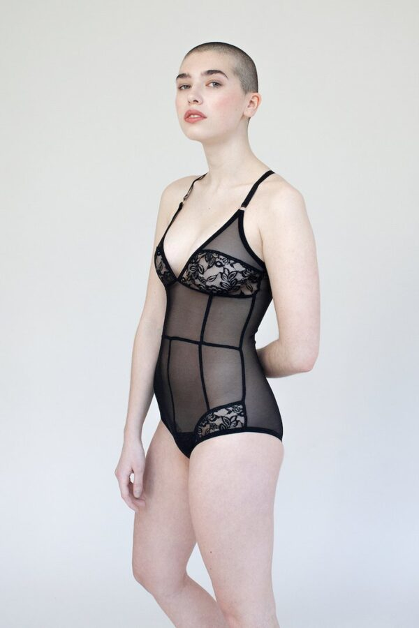A young lady stands wearing the Iona bodysuit- a mesh and lace paneled black sheer bodysuit with adjustable straps and seams flattering the body.